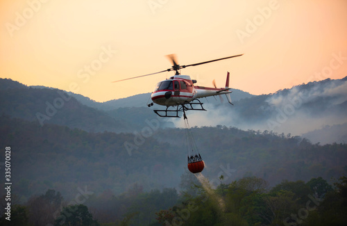 Fotografía The helicopter is drawing water from the reservoir and will be watered to extinguish the burning forest in the mountains