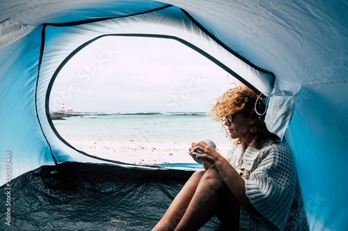 Fototapeta Alternative travel lifestyle adventure with adult caucasian woman inside a tent camping at the beach with blue ocean and sky view - freedom concept and positive vibes - obraz