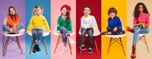 Cheerful kids in stylish clothes sitting on chairs Canvas Print
