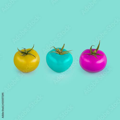Photo Three tomatos with strange color on blue background