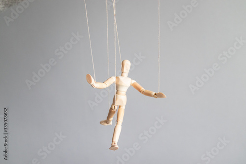Photo Human hand holds a wooden doll on the clothesline on a gray background