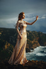 Beautiful Red-haired Girl In A Gold Dress And Crown Stands On The Shore Of The Ocean