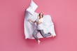 Full size photo of funny lady jump high throw pillow up blanket flight rejoicing slumber party wear sleep mask white t-shirt plaid pajama pants barefoot isolated pink color background