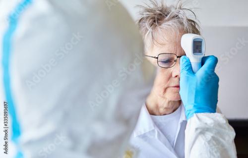 Obraz Measure fever in senior citizens in the nursing home because of Covid-19 - fototapety do salonu