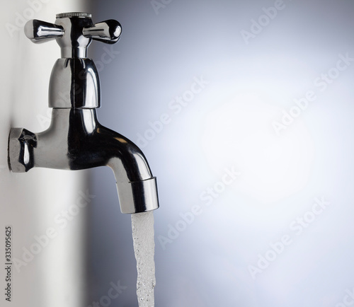 Leinwand Poster Drain water from the Metal tap, Water flowing from modern faucet