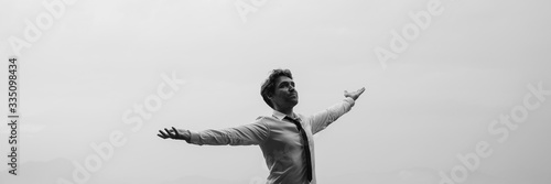 Photo Businessman standing under grey sky with his arms spread