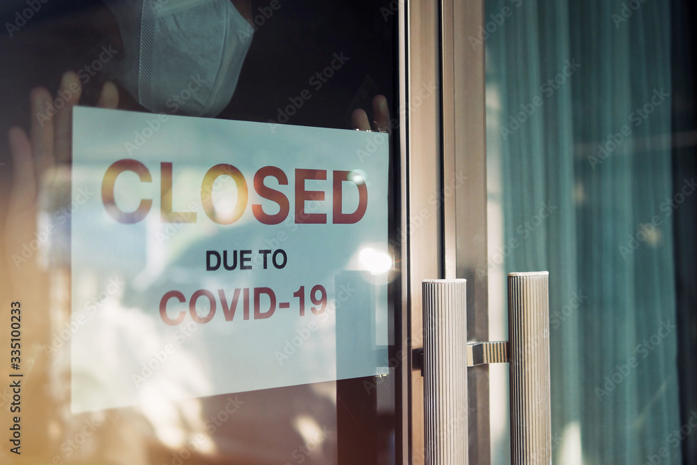 Fototapeta Business office or store shop is closed, bankrupt business due to the effect of novel Coronavirus (COVID-19) pandemic. Unidentified person wearing mask hanging closed sign in background on front door.