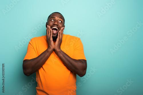 Carta da parati Joyful and happy afro guy over cyan background