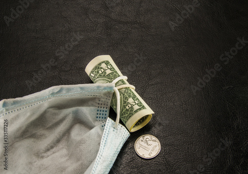 Fototapeta face mask dollar and ruble on a black background,coronavirus facial mask ruble, dollars and coronavirus, protection mask on a black background with money obraz