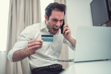 Handsome businessman are furious with credit card and mobile.