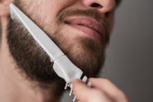 A Man Combing His Beard With A...