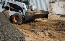White Skid Steer Loader At A C...