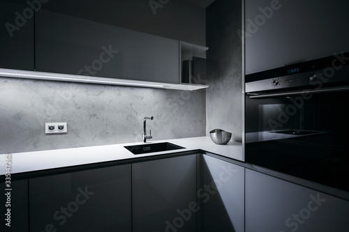 Modern white kitchen in minimalist design, in night, with light strip turned on, modern oven, granite sink, wall-sockets and premium materials such as glass, concrete, aluminum and stainless steel. - fototapety na wymiar