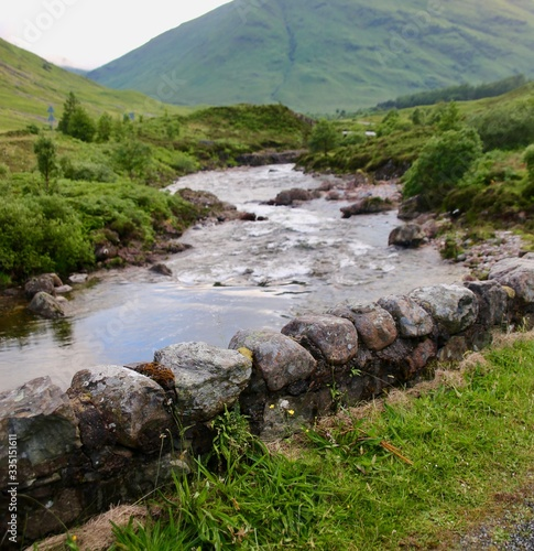 Stone rock wall bordering a babbling brook in Scotland Canvas Print