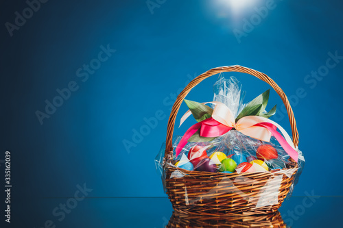 Foto Easter gift basket with multicolor eggs, blue background