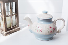 Vintage Tea-ware Pale Blue Color On White Table. Tea Pot And Cup With Painted Roses