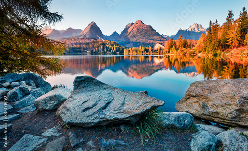Fototapeta Last sunlight glowing of mountain hills on Strbske pleso lake. Exciting evening scene of High Tatras National Park, Slovakia, Europe. Beauty of nature concept background. obraz