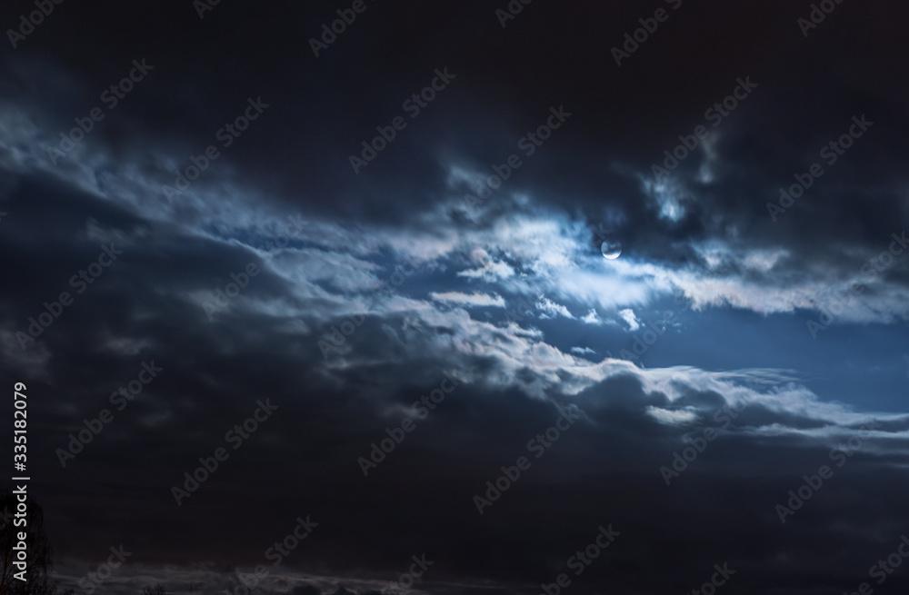 Fototapeta Mond hinter Wolken, diagonal aufgerissen, leuchtend, bläulich, kalt