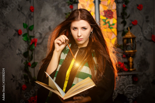 A young woman in a black mantle with a striped scarf around her neck casts a spell from a book and conjures with a wand of magic Canvas-taulu
