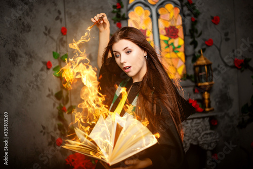 Foto A young woman in a black mantle with a striped scarf around her neck casts a spell from a book and conjures with a wand of magic