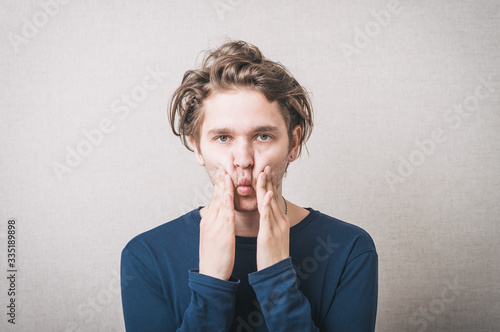 Photo Young man squeezing her cheeks with her hands