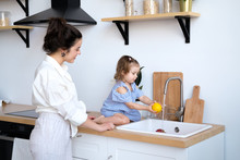 A Beautiful Young Woman With Her Two Year Old Daughter Is Washing Fruit In The Kitchen Sink. Fresh Bright Fruits, Apples, Oranges, Pears. Healthy Food For Children. The Baby Helps Her Mother.