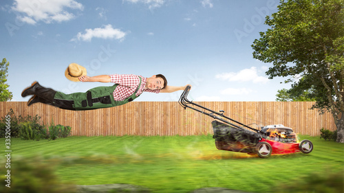 Fotografiet Funny gardener with a powerful lawn mower