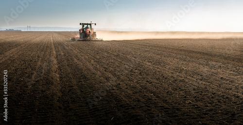 Obraz Tractor is preparing the land at dusk - fototapety do salonu