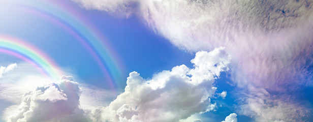Beautiful double rainbow Cloudscape Background - awesome blue sky with pretty clouds and a large double rainbow arcing across the left corner with copy space