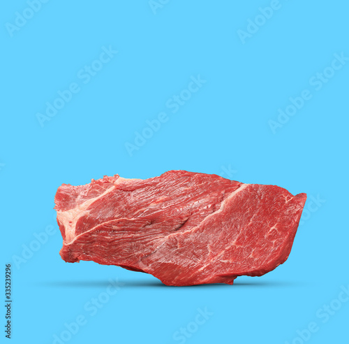 Fotografia raw red beef meat isolated on a blue background