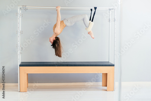Valokuva Pretty Pilates Instructor Hanging Upside Down from Trapeze Table
