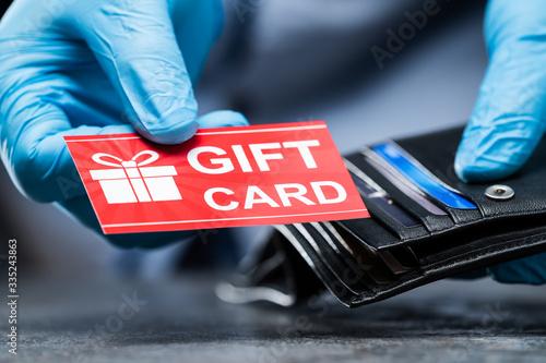 Fotografía Consumer Taking Gift Card From Wallet In Gloves