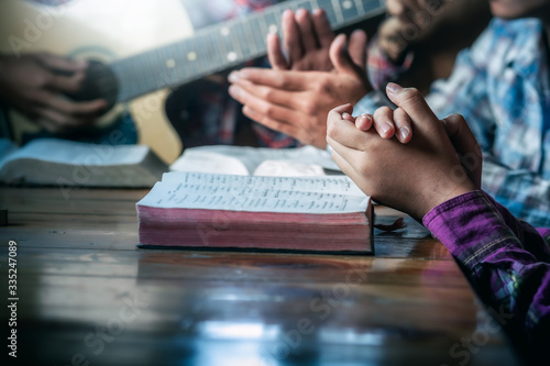 Leinwand Poster Group of christian sitting praying and worship God by playing guitar and sing a song together in home, christian worship meeting concept