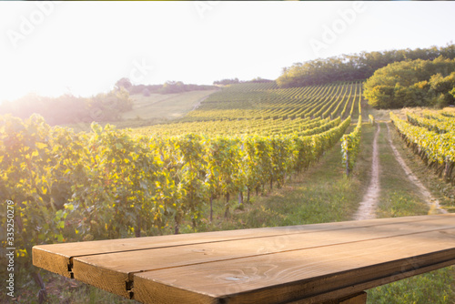 Fotomural Brown wood table in autumn vineyard landscape with empty copy space on the table for product display mockup