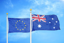 European Union And Australia Two Flags On Flagpoles And Blue Cloudy Sky