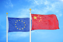 European Union And China Two Flags On Flagpoles And Blue Cloudy Sky