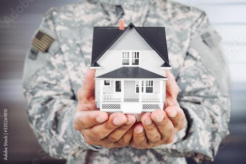 Obraz Soldier man holding a model of the house - fototapety do salonu