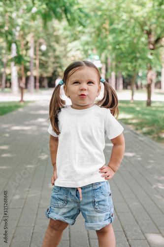 smiling little girl in blank white t-shirt standing in park Canvas Print