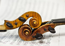 Two Violins On A  Sheet Music Background. Violin Heads