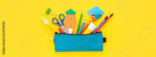 Obraz Pencil case and school supplies inside on yellow background. Back to school creative flat lay.    - fototapety do salonu