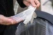 Closeup of hands of woman putting used latex gloves in the garbage in the street