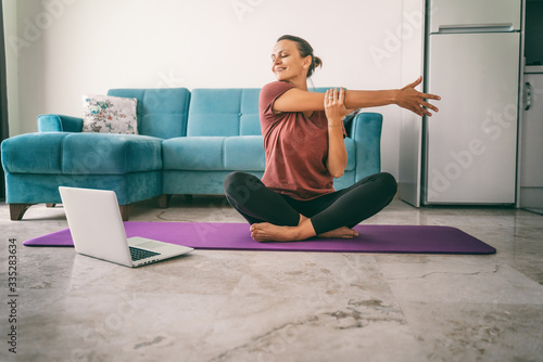 Attractive young woman doing yoga stretching yoga online at home Fototapet
