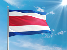 Costa Rica National Flag Waving In The Wind Against Deep Blue Sky. High Quality Fabric. International Relations Concept.