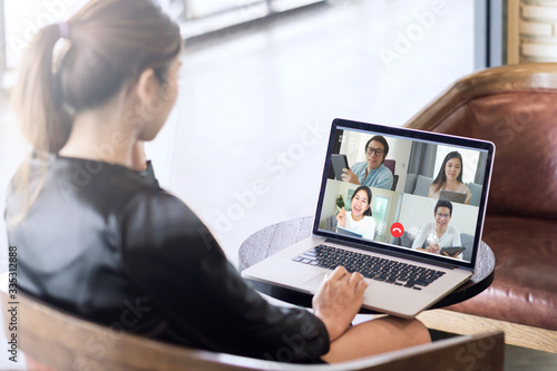 Obraz Back view of business woman talking about sale report in video conference. Asian team using laptop and tablet online meeting in video call.Working from home, Working remotely and Social isolation. - fototapety do salonu
