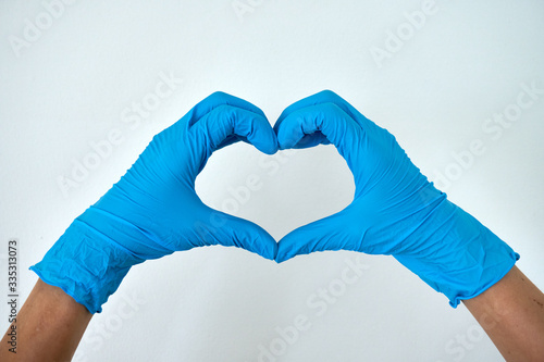 Photo Human rising hands make finger heart shape wearing blue disposable latex glove,