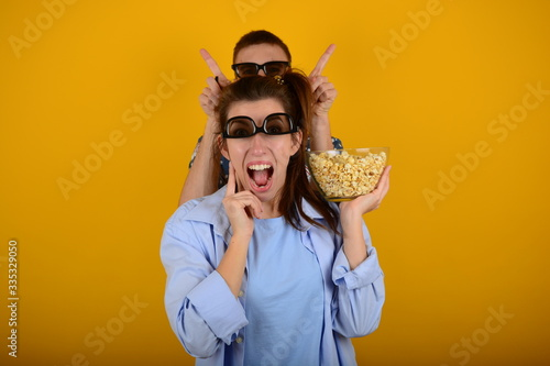 Платно Crazy young couple in cinema on a yellow background