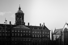 Low Angle Greyscale Shot Of The Royal Palace At The Dam Square In Amsterdam, Netherlands
