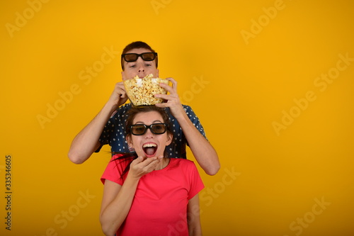 Платно woman and man with popcorn in their hands watching a movie