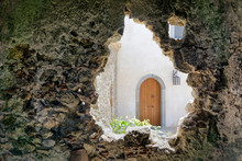 View On A Wooden Door Of A New House Through The Opening In The Wall Of An Old Ruined Building