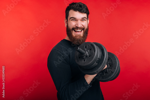 Photo of smiling man with beard looking at the camera and working with dumbbell Tablou Canvas